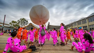 Group of people in pink onesies playing with large inflatable ball