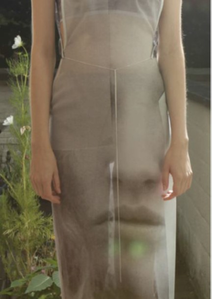 Model wearing grey dress emblazoned with human nose and mouth