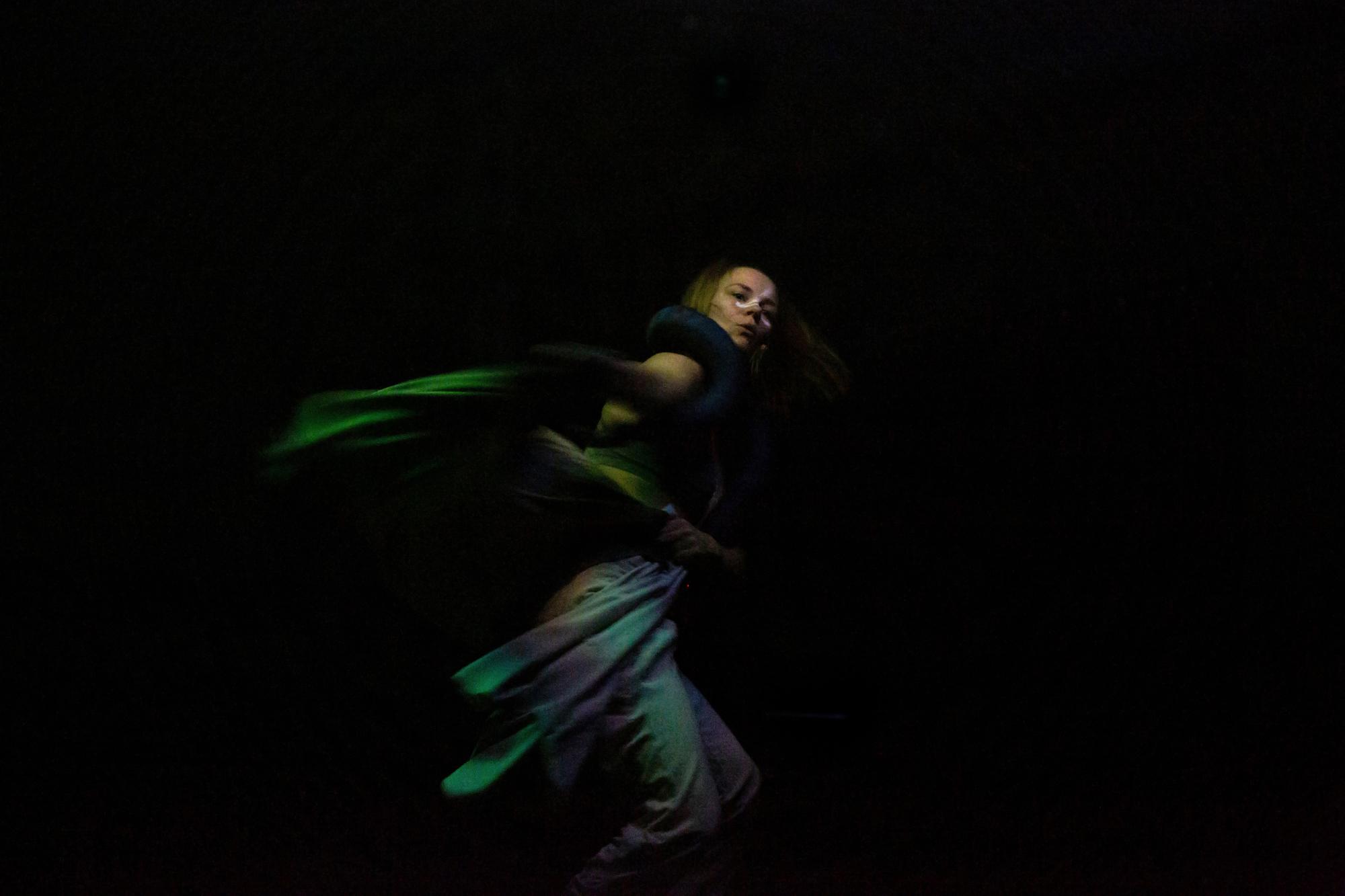 Costumed dancer against black backdrop